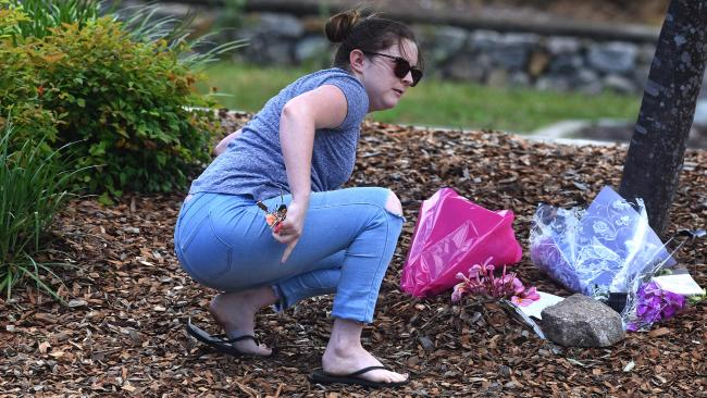 A woman places flowers at the site of the accident. Picture: AAP/John Gass