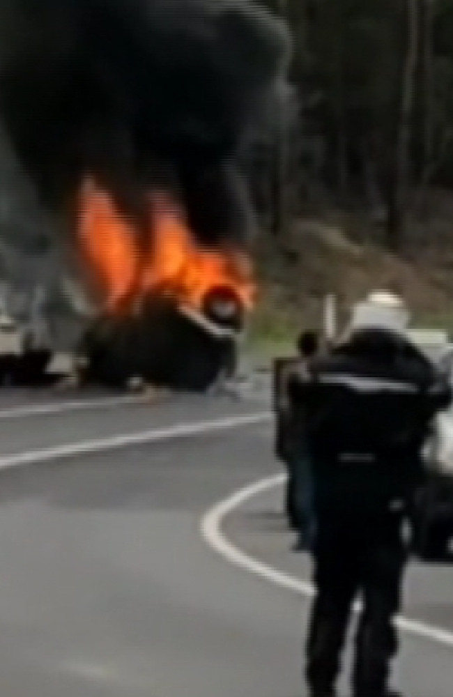Horror scene... Motorists look on as vehicle explodes into flames. Picture: Nine News