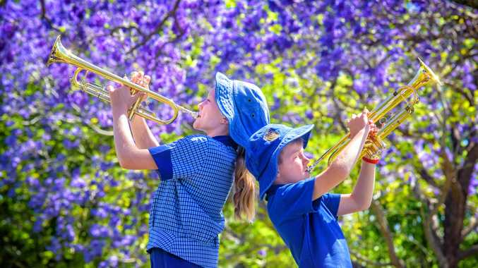 Erica Power, 11 and Cooper Stephenson, 8 of Grafton Public School sound the trumpet during a break from the school concert held in See Park for the Jacaranda Festival.