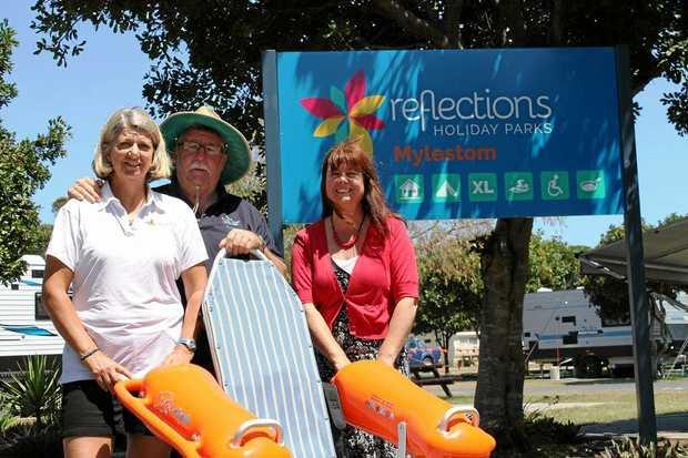 BEACH ACCESS: Chris and Dianna Donohue with Anna Joy and the floating beach wheelchair.