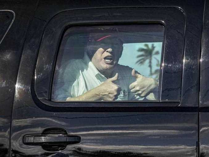 Donald Trump gives two thumbs up to cheering supporters from his motorcade heading to his Mar-a-Lago estate after spending the morning at Trump International Golf Club, Friday, Dec. 29, 2017, in West Palm Beach, Fla.
