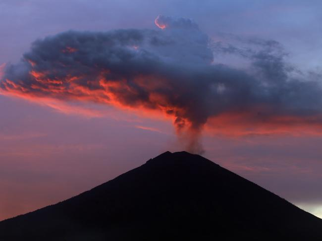 Clouds of ash from Mount Agung volcano are lit with warm sunset light in Karangasem, Bali, Indonesia, in November, 2017. Picture: Firdia Lisnawati