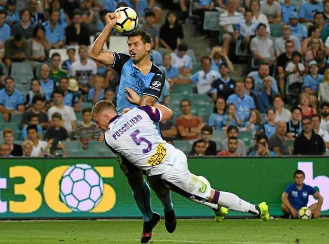 Sydney FC star Bobo is brought down in the box by Perth rival Jacob Poscoliero.