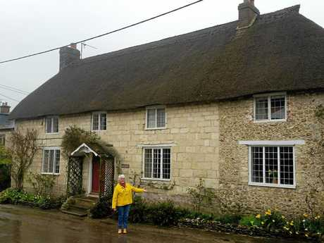 Coast resident Gwenda Tudman inspects a home in the English village of Cattistock during filming of an episode of Escape to the Country.