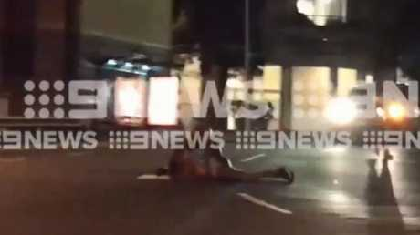 A man in a white cap appears to push over the victim and repeatedly punch him on the ground. Picture: Channel 9