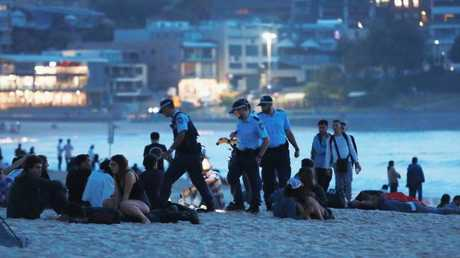 Police check revellers for alcohol before dawn on Bondi Beach in Sydney. Picture: Mark Evans