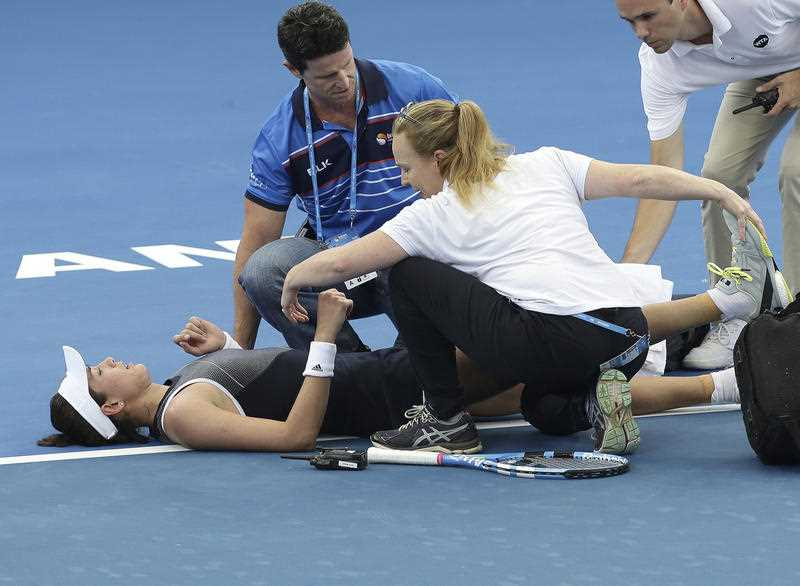 Garbine Muguruza of Spain is treated by medical staff after she suffered cramps in her match against Aleksandra Krunic of Serbia during the Brisbane International tennis tournament in Brisbane, Australia, Tuesday, Jan. 2, 2018. Muguruza fell to the court behind the baseline in the third set before retiring from her opening match.