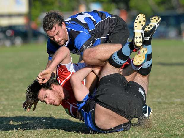 AIMING HIGH: Maroochydore Swans player Rick Portingale (top) makes a tackle against the Nambour Toads at Cotton Tree.