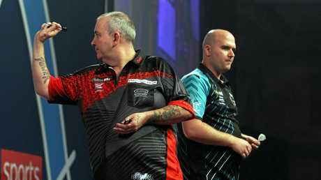 Phil 'Power' Taylor (L) takes aim in the world darts final against Rob Cross.