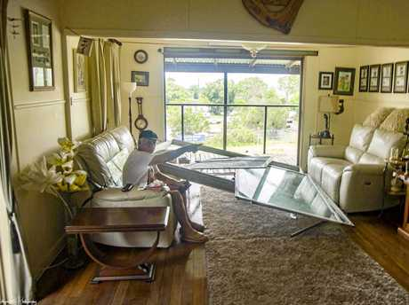 Ray Mahoney-Smith sits in his living room where the force of the storm pushed in their sliding glass door and wrecked furnitute