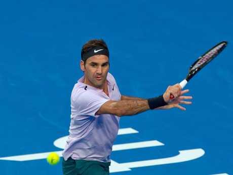 Roger Federer hits a slice return against Karen Khachanov.
