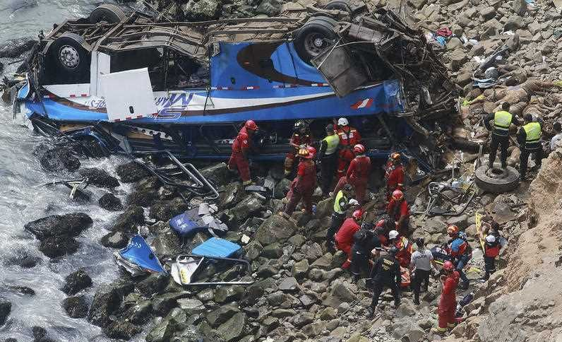 Firemen recover bodies from a bus that fell off a cliff after it was hit by a tractor-trailer rig, in Pasamayo, Peru.