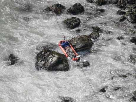 An injured man is transported over water from a bus that fell off a cliff after it was hit by a tractor-trailer rig, in Pasamayo, Peru, Tuesday, Jan. 2, 2018