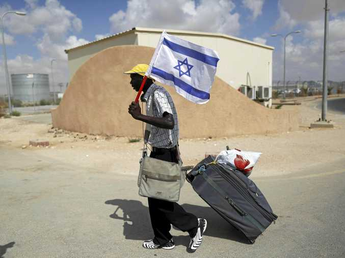 An African migrant carries an Israeli flag following his court-ordered release from the Israeli Holot Detention facility, which is located near the Israeli-Egyptian border.