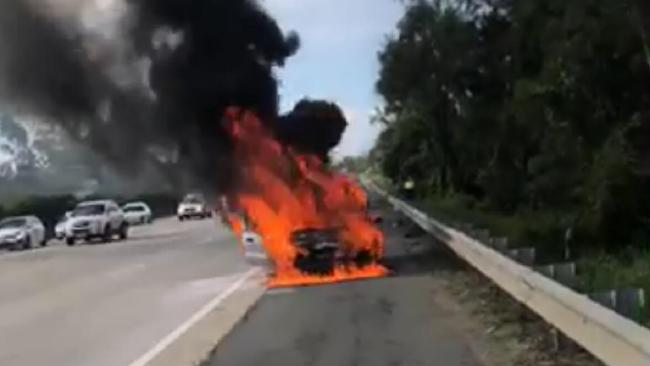 A car burst into flames on the M1 at Yatala. Photo: Brooke Stewart
