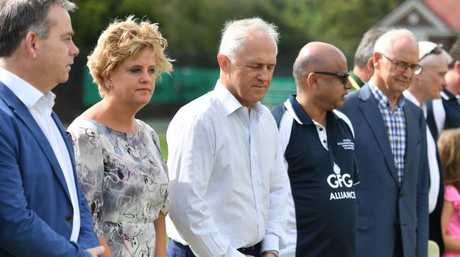 Britain's High Commissioner Menna Rawlings, Prime Minister Malcolm Turnbull and Indian businessman Sanjeev Gupta hold a minute's silence for the victims of a seaplane crash, at a cricket match between Australian and British parliamentarians at Scots College in Sydney. Picture: AAP Image/Mick Tsikas