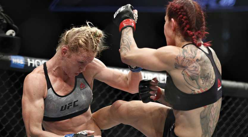 Cris Cyborg kicks Holly Holm during a featherweight championship mixed martial arts bout at UFC 219, Saturday, Dec. 30, 2017, in Las Vegas