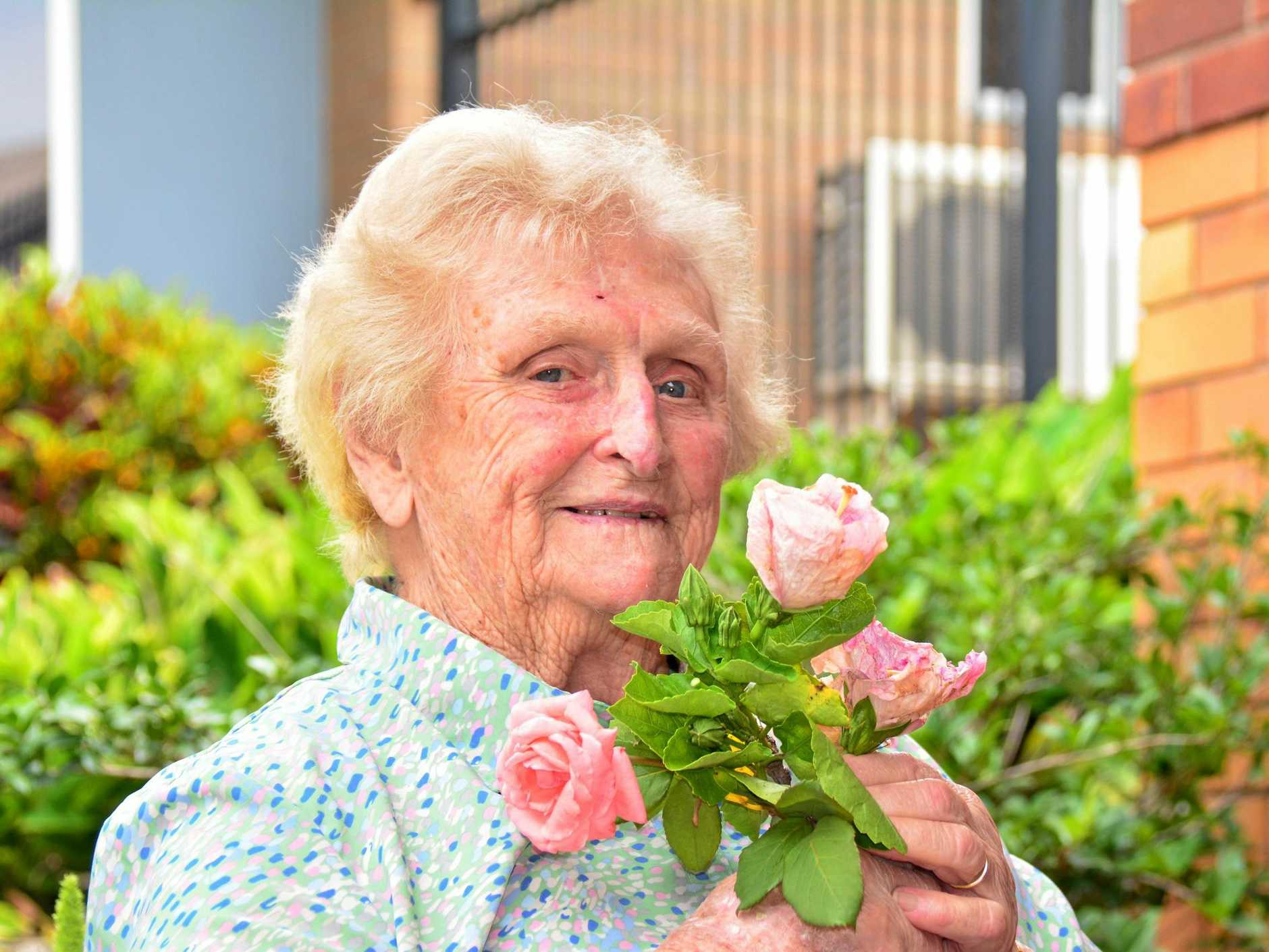 Lady Flo enjoying the pink hibiscus named after her.  Photo Kate Darvall/ South Burnett Times