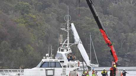 NSW police and salvage personnel work to recover the wreckage of the wing of the seaplane that crashed into Jerusalem Bay. Picture: Mick Tsikas