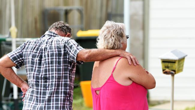 Stephen Taylor was crushed to death by a brick wall while working on his car out the front of his house in Thuringowa Central. Family and friends of the victim console each other at the scene. Picture: Zak Simmonds