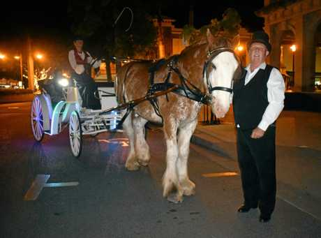 Cherie Dooley at the reigns with Capricorn Carriages ownere Steven May and Kenny the Clydesdale in the Rockhampton CBD for their first horse-drawn carriage ride on Friday night.
