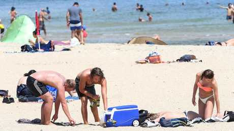 Hot weather in Melbourne. Sunbathers cool off with some drinks at South Melbourne beach. Picture: Ian Currie