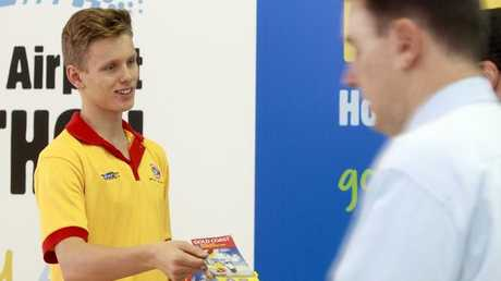 A volunteer surf lifesaver handing out surf safety tips to tourists at Gold Coast Airport.