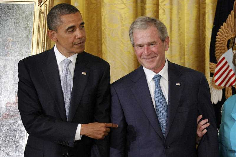 President Barack Obama points to former President George W. Bush during a ceremony to unveil his official portrait, Thursday, May 31, 2012, in the East Room at the White House in Washington.