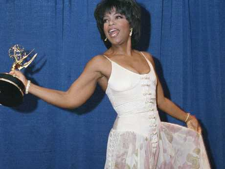 Oprah Winfrey clutching her Emmy for outstanding talk show host at the 21st Annual Daytime Emmy Awards.