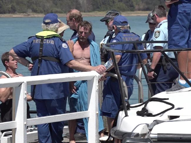 The remaining two men are escorted to shore by Marine Rescue volunteers. Pictures: TVN