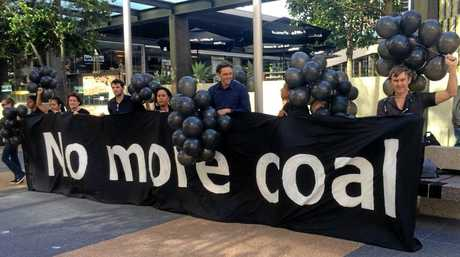 Protesters armed with black balloons stood outside a Brisbane Court Case to show their support for a court case against mining company Adani.