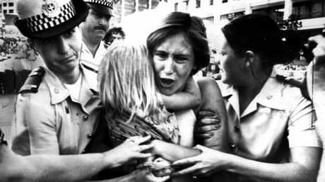 A woman protester is taken away by police officers during a march against proposed state government legislation to ban street demonstrations, in Brisbane Sept 22, 1977.