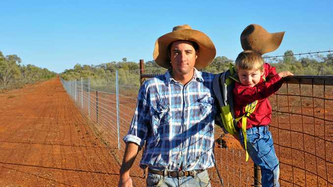 STEPPING UP: Wool producer Donald Truss from Toompine, south of Quilpie, with his son Henry and a stretch of the wild dog exclusion fencing on his property.