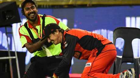 Brad Hogg of the Melbourne Renegades hides with the security guard after dropping a catch