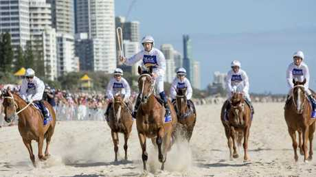 Champion jockey Hugh Bowman holds the Queen's baton aloft as he rides along Surfers. Picture: Tim Marsden