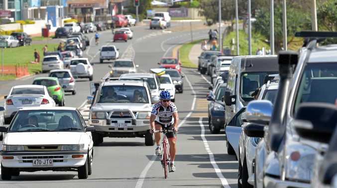 A cyclist rides on the road with busy traffic at Alexandra Headland.