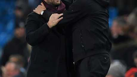 Manchester City's Spanish manager Pep Guardiola (R) consoles Bristol City's English manager Lee Johnson