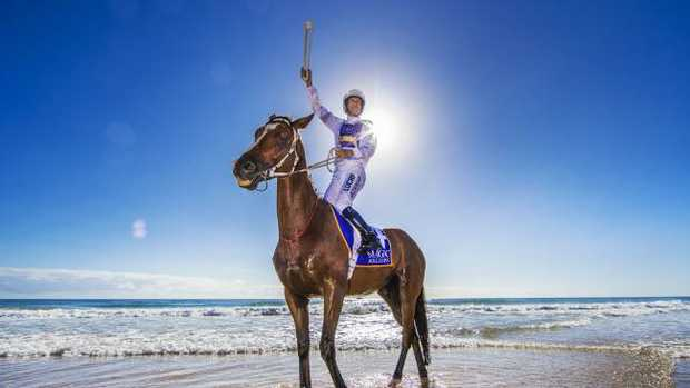 Magic Millions horses on the beach at Surfers Paradise for the barrier draw and Commonwealth Games baton relay arrival. Champion jockey Hugh Bowman, carrying the Queen's Baton. Picture: Nigel Hallett.