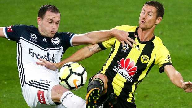 Melbourne Victory's Leigh Broxham (left) and Wellington's Nathan Burns compete for the ball.