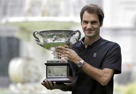 Switzerland's Roger Federer poses for photos with his Australian Open trophy at Carlton Gardens in Melbourne, Australia, Monday, Jan. 30, 2017. Federer defeated Spain's Rafael Nadal in their men's final at the Australian Open tennis championships on Sunday.