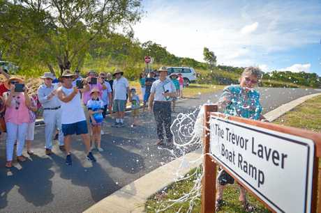 Betty Laver breaks the champagne over the sign at the naming of the Toolooa boat ramp in honour of Trevor Laver.