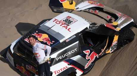 Sebastien Loeb stands next to his Peugeot.