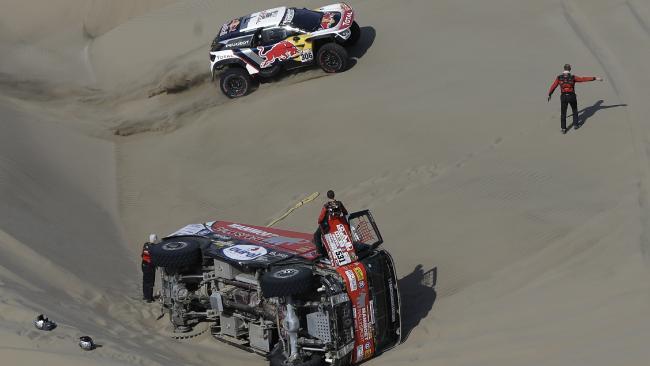 Sebastien Loeb race past the overturned truck of Janus Van Kasteren.