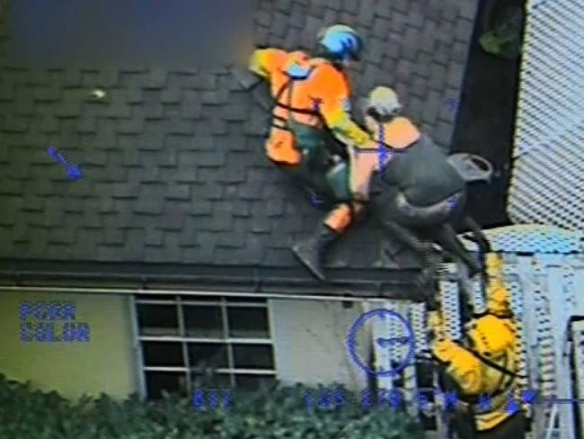 US Coast Guard officials rescue a family including a young child from their home that was severely damaged after a mudslide. Picture: Supplied