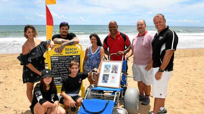 Annie and Billy Clark (front), Bindi Balazs, Jay Balazs, Kara Clark, Moe Turaga, Dave Facer and surf club president John McGregor (back) with the donated chair.