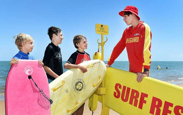 STAYING SAFE: Lifeguard Liam Farrelly talks with (L) Seth Keal,9, Saxon Herrmann,12, and Angus Keal,11, at Torquay Beach.