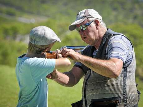 ON TARGET: Peter Purkis helps youngster Jordan find his aim at Gladstone Clay Target Club. The club will hold its first shooting meet of the year tomorrow.
