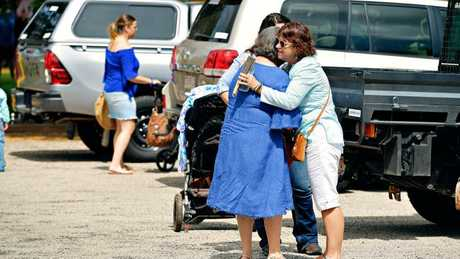 Hugs are exchanged at Casuarina Street Primary School as mourners arrive for Dolly Everett's memorial service in Katherine Northern Territory