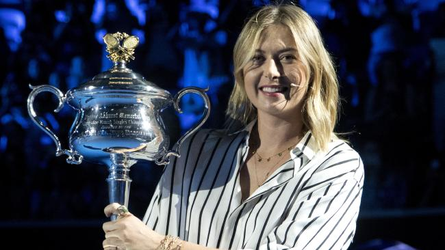 Former ladies single's champion Russia's Maria Sharapova poses for a photo with the Daphne Akhurst Memorial Cup on Margaret Court Arena during the ceremony for the official draw at the Australian Open tennis championships in Melbourne, Australia Thursday, Jan. 11, 2018. (AP Photo/Mark Baker)