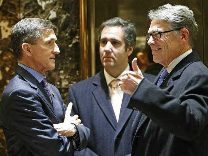 Retired U.S. Army Lieutenant General Michael T. Flynn, left, chats with former Texas Gov. Rick Perry, right, and Trump attorney Michael D. Cohen, center, in the lobby at Trump Tower, Monday, Dec. 12, 2016, in New York.